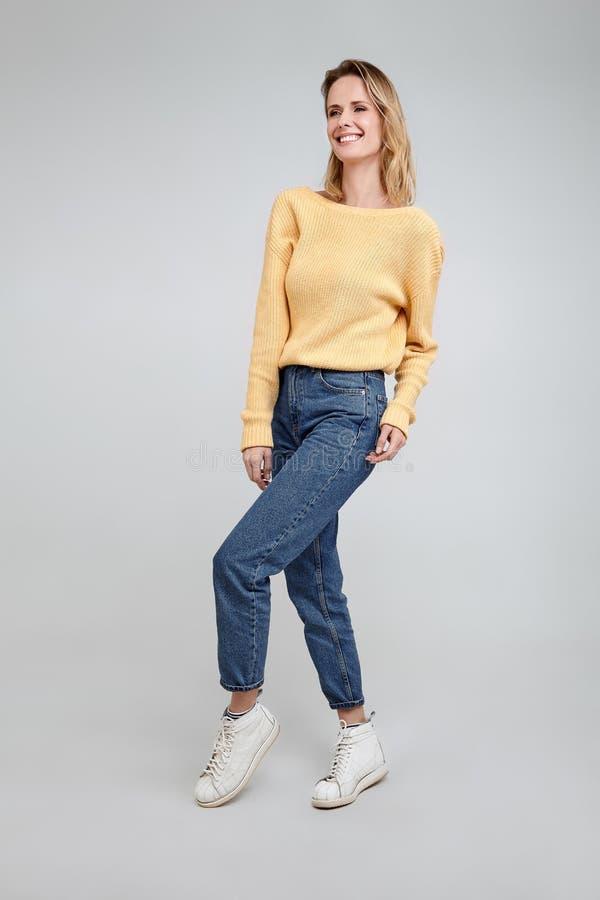 Eine Ganzaufnahme einer schönen Blondine, gekleidet in der stilvollen Kleidung Haltungen vor dem weißen Hintergrund lizenzfreies stockbild