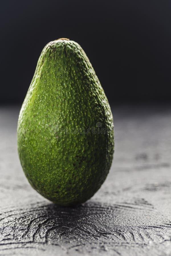 Eine ganze Avocado auf einer dunklen Hintergrundnahaufnahme mit copyspace stockbilder