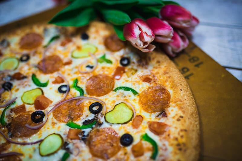 Eine ganze Pizza mit Oliven, Tomaten, Käse, Gurken auf dem Tisch mit roten Tulpen lizenzfreie stockbilder