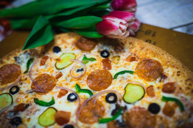 Eine ganze Pizza mit Oliven, Tomaten, Käse, Gurken auf dem Tisch mit roten Tulpen stockbild