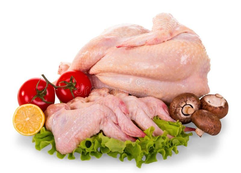 Eine ganze rohe Hühnerkarkasse und Flügel, Tomaten, Pilze, lemo stockbild