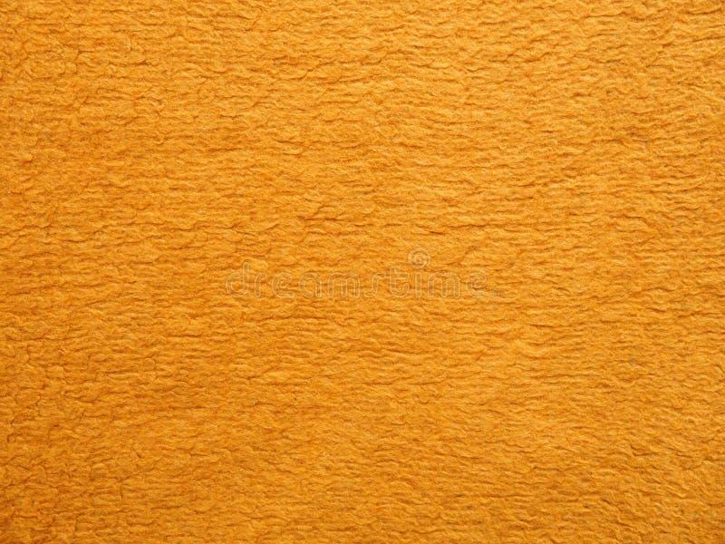 Eine Ganzseite des orange Fauxpelzes, flaumiges Material Ansicht der Spitze auf Hintergrundbeschaffenheitsnahaufnahme, synthetisc stockfotos