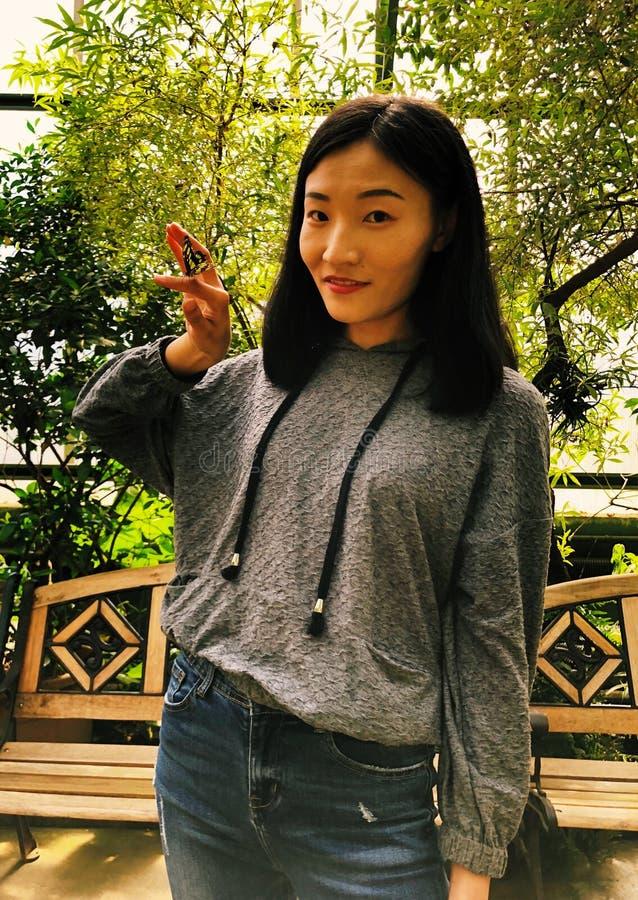 Eine gelbe Reispapier-Schmetterlingslandung auf einem asiatischen Frauenfinger lizenzfreie stockbilder