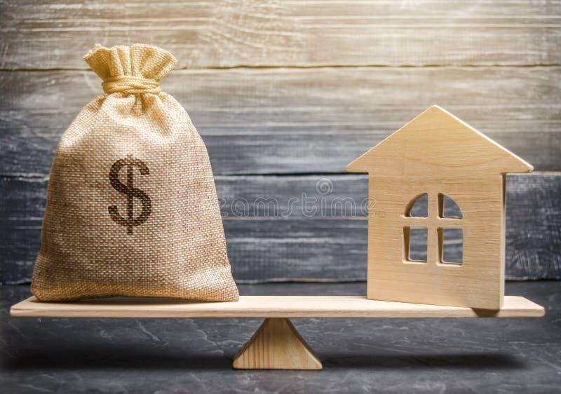 Eine Geldtasche und ein Holzhaus auf den Skalen Das Konzept des Immobilienkaufs Verkauf des Eigentums Zahlung der Hypothek stockfoto