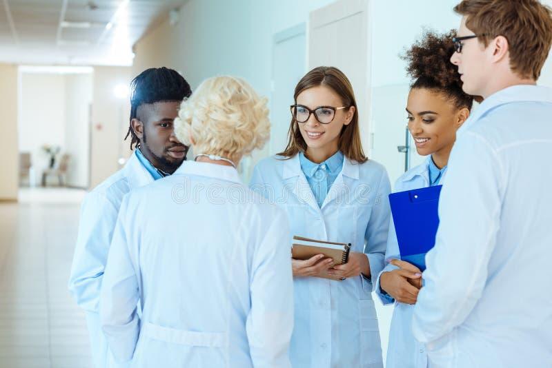 Eine gemischtrassige Gruppe medizinische Internierten in den Laborkitteln Arbeit besprechend lizenzfreies stockfoto