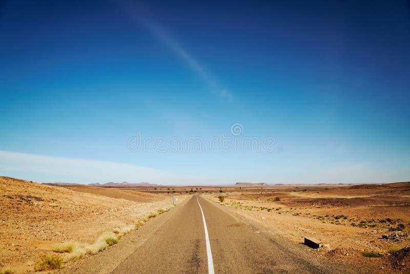 Eine gerade endlose Straße in der Wüste lizenzfreie stockbilder