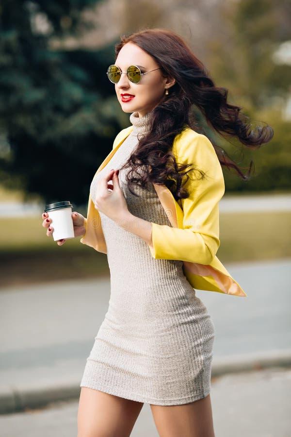 Eine Geschäftsfrau, die über Handy spricht und eine Kaffeetasse hält Junges dünnes stilvolles Mädchen in der hellen Kleidung, gel lizenzfreies stockbild