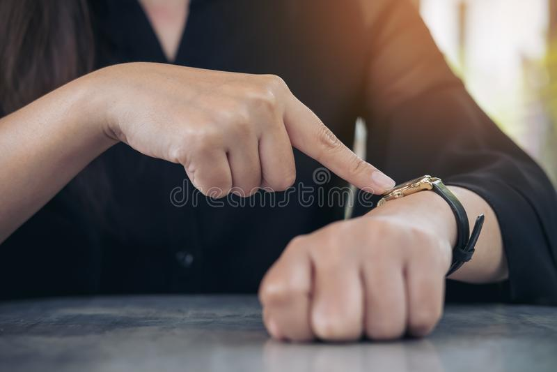 Eine Geschäftsfrau, die auf eine schwarze Armbanduhr auf ihrem Arm in der Arbeitszeit beim Warten auf jemand zeigt lizenzfreies stockbild