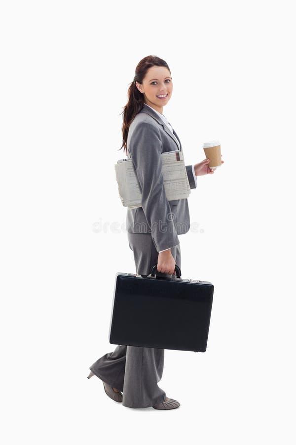Eine Geschäftsfrau, die mit einem Aktenkoffer geht lizenzfreies stockbild
