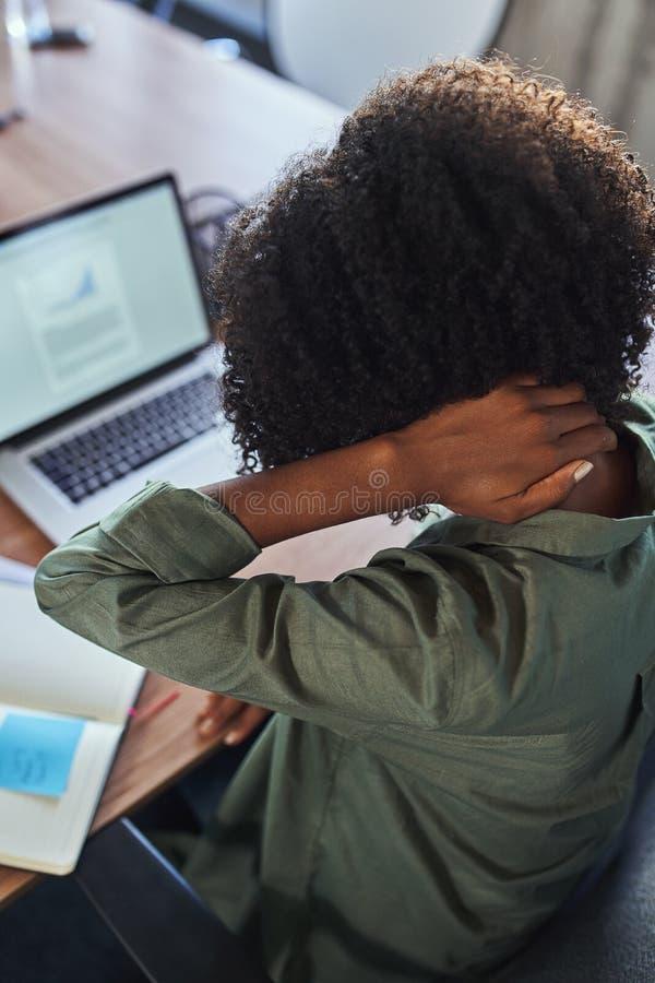 Eine Geschäftsfrau, die unter den Schmerz im Hals im Büro leidet lizenzfreies stockbild