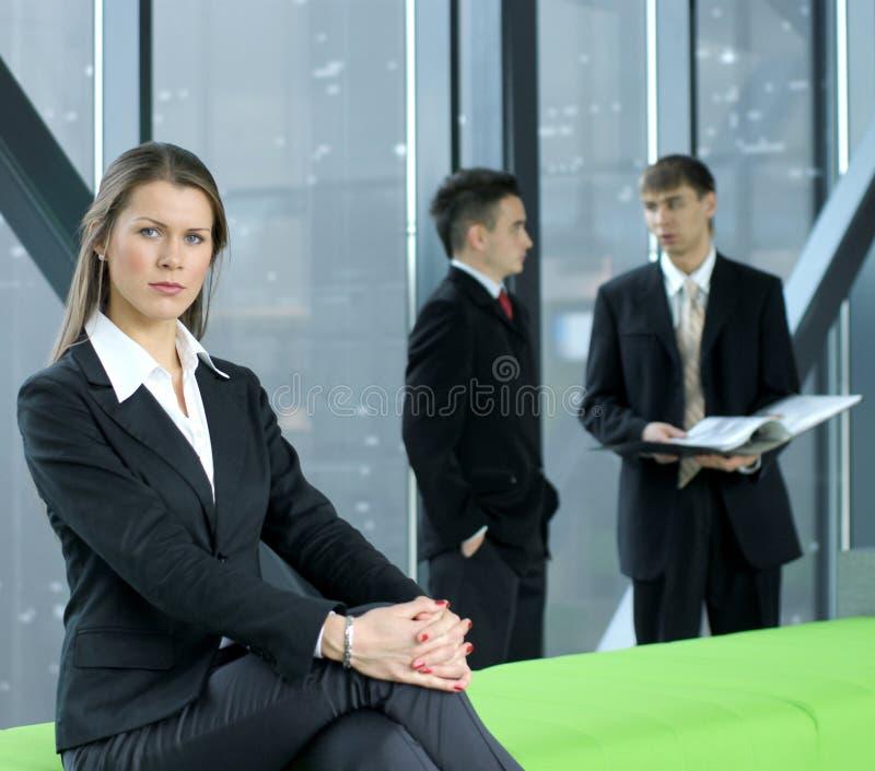 Eine Geschäftsfrau sitzt vor ihren Kollegen lizenzfreie stockfotos