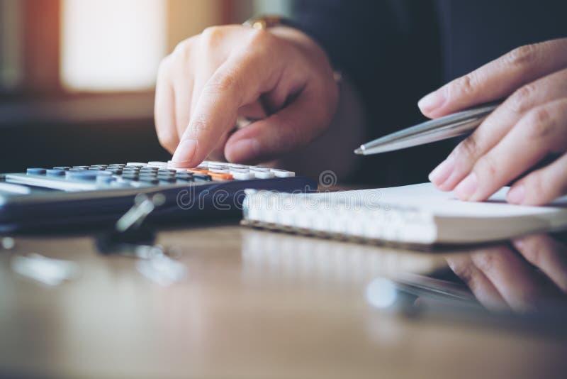 Eine Geschäftsfraufunktion, unter Verwendung des Taschenrechners und des Schreibens auf Notizbuch im Büro stockbilder