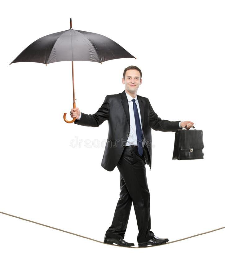 Eine Geschäftsperson, die einen Regenschirm anhält stockfotos