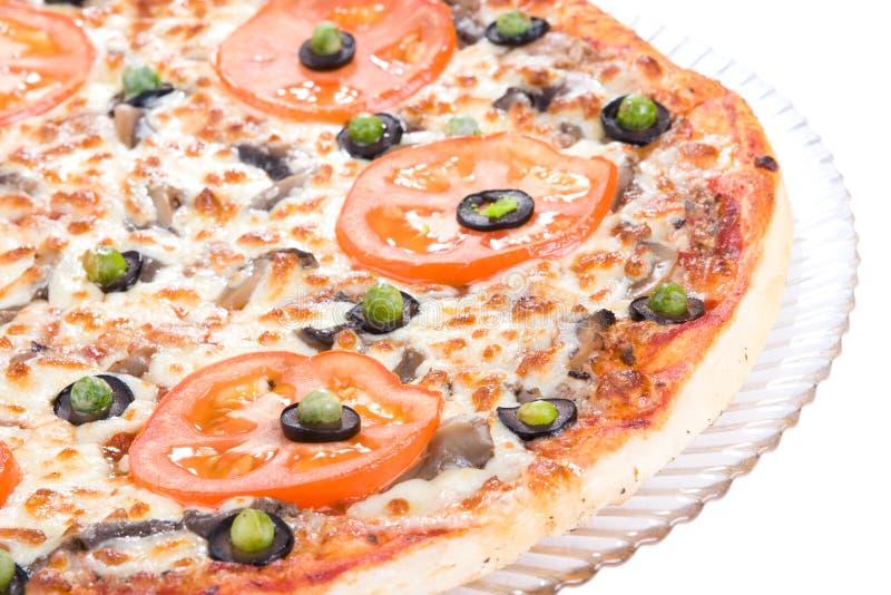 Eine geschmackvolle Pizza auf der Platte lizenzfreies stockbild