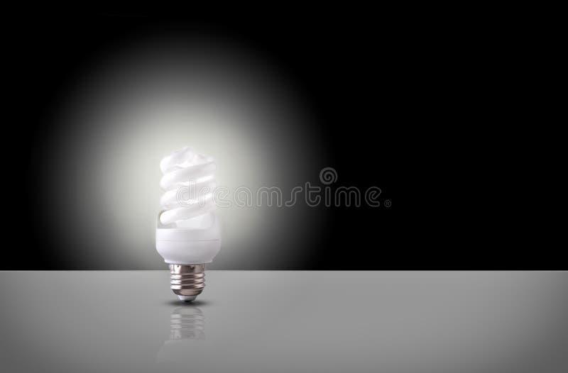 Eine gewundene Glühlampe auf schwarzem Hintergrund stock abbildung
