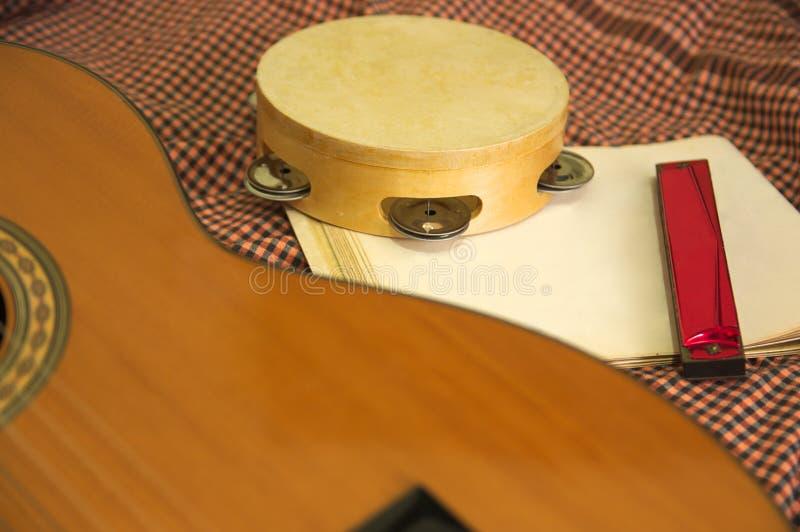 Eine Gitarre, ein Tamburin und Noten stockbilder