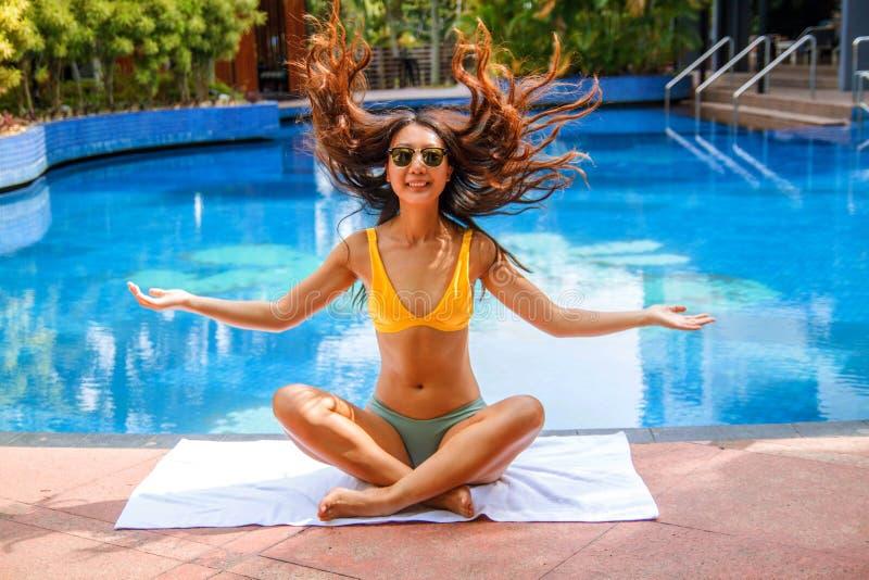 Eine glückliche asiatische Frau, die einen Bikini trägt und auf der Seite eines Swimmingpools sich entspannt lizenzfreies stockfoto