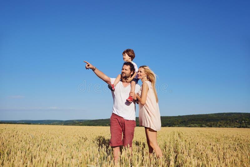 Eine glückliche Familie, die auf einem Weizengebiet steht lizenzfreie stockbilder