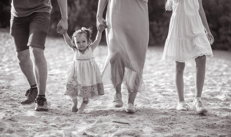 Eine glückliche Familie mit wenigem Baby geht und hält Hände beim Gehen stockfoto
