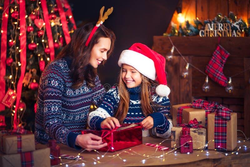 Eine glückliche Familienmutter und -kind verpacken Weihnachtsgeschenke lizenzfreie stockfotos