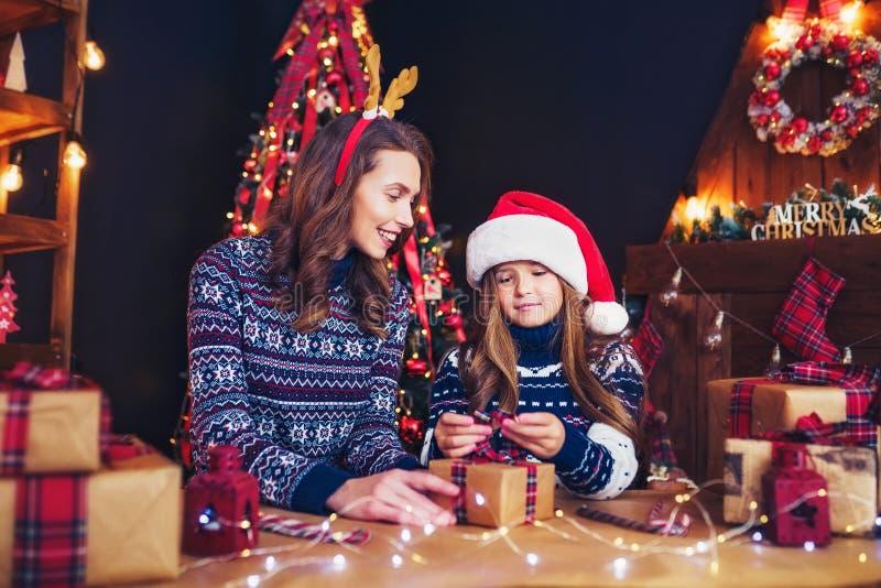 Eine glückliche Familienmutter und -kind verpacken Weihnachtsgeschenke stockfotos