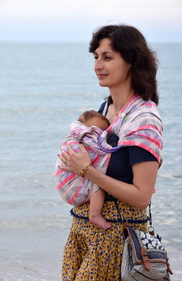 Eine glückliche lächelnde junge Frau, die ihr neugeborenes Baby in einem Riemen trägt lizenzfreie stockfotografie