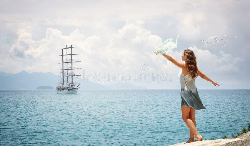 Eine glückliche romantische Frau trifft ein Segelschiff auf dem Uferwellenartig bewegen lizenzfreie stockbilder