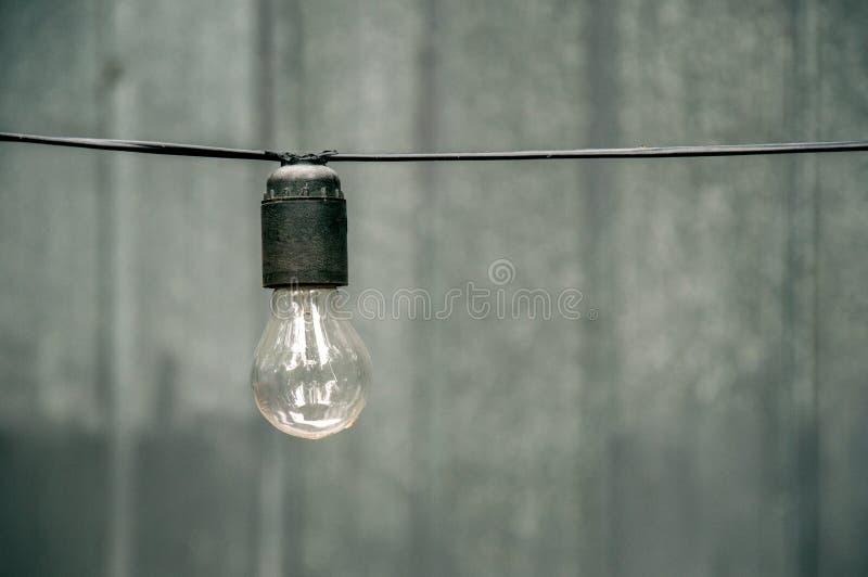 Eine Glühlampe auf dem horizontalen Draht nach dem Herbstregen Element einer Straßengirlande stockbilder