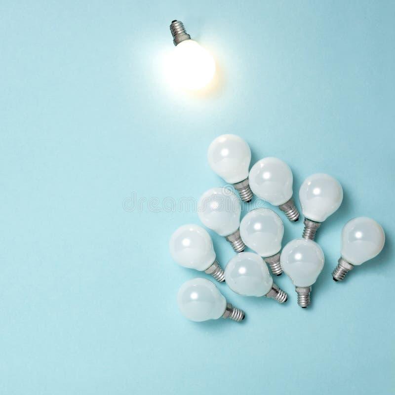 Eine Glühlampe hervorragend, glühend unterschiedlich Geschäftskreativitäts-Ideenkonzepte stockfoto