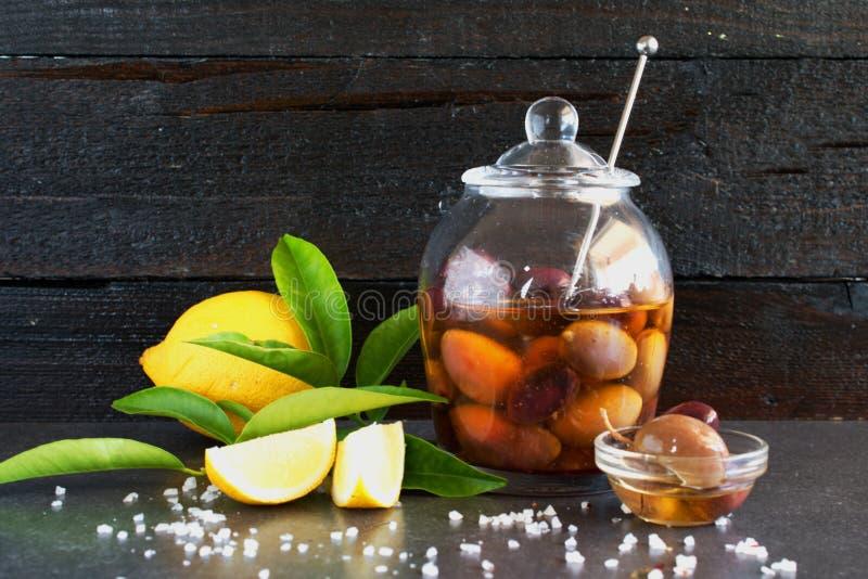 Eine Glasschüssel mit Oliven im Olivenöl auf einem hölzernen Hintergrund mit Zitrone, Seesalz Traditionelles griechisches Lebensm lizenzfreies stockfoto