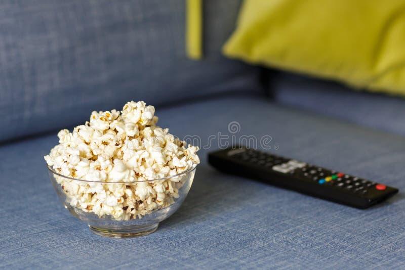 Eine Glassch?ssel Popcorn und Fernbedienung Gl?ttung gem?tlich, einen Film oder Fernsehserie zu Hause aufpassend stockbild