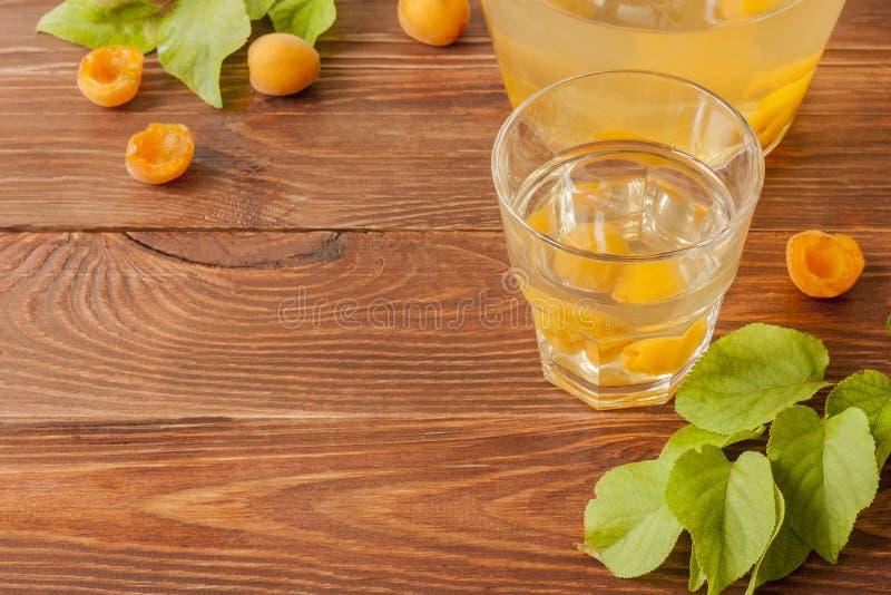Eine Glasschale und ein Krug mit AprikosenObstkompott und reifen Aprikosen auf einem Holztisch S??er und gesunder Nachtisch Kopie stockfotografie