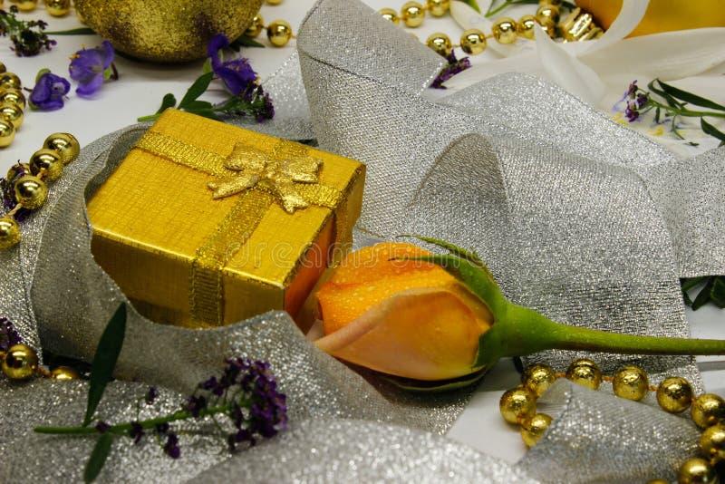 Eine goldene Geschenkbox und eine Rose eingewickelt im silbernen Band stockfoto