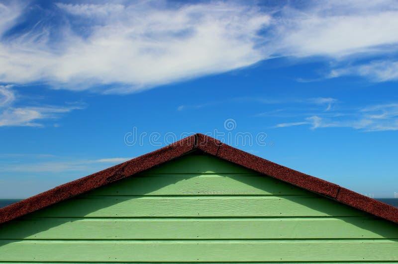 Eine grüne Strandhütte gegenüber einem hellblauen Himmel stockfotografie
