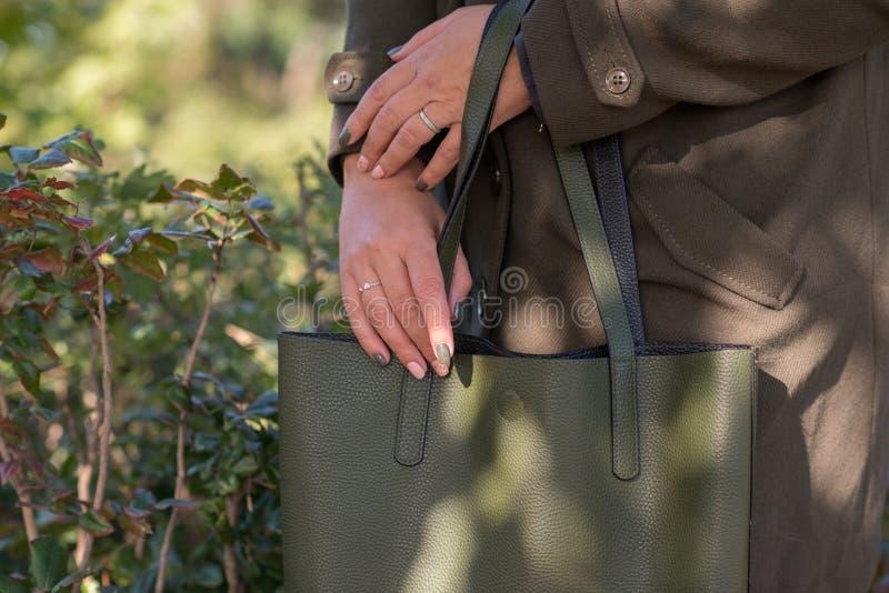 Eine grüne Tasche in den Händen stockbilder