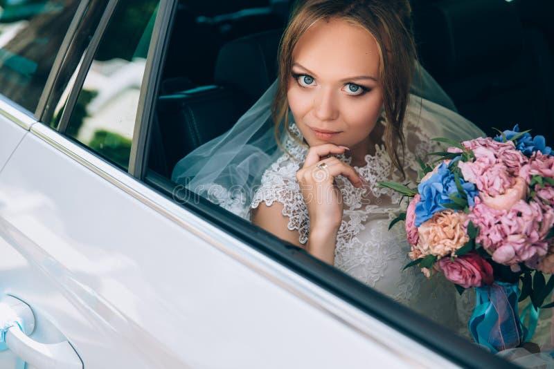 Eine grau-äugige Blondine in einem Hochzeitskleid sitzt im Auto Porträt eines hübschen Mädchens mit Make-up und ein Blumenstrauß  stockfotos