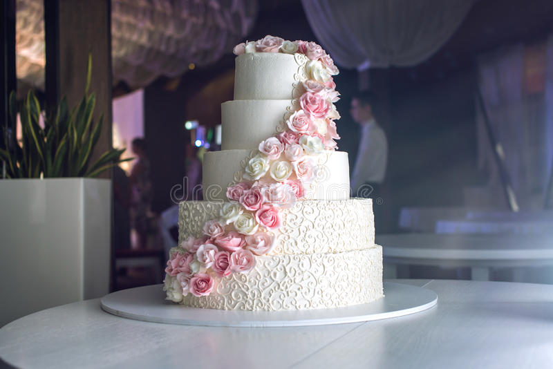 Eine große abgestufte Hochzeitstorte auf dem Tisch verziert mit rosa Rosen im Restaurant lizenzfreie stockfotos