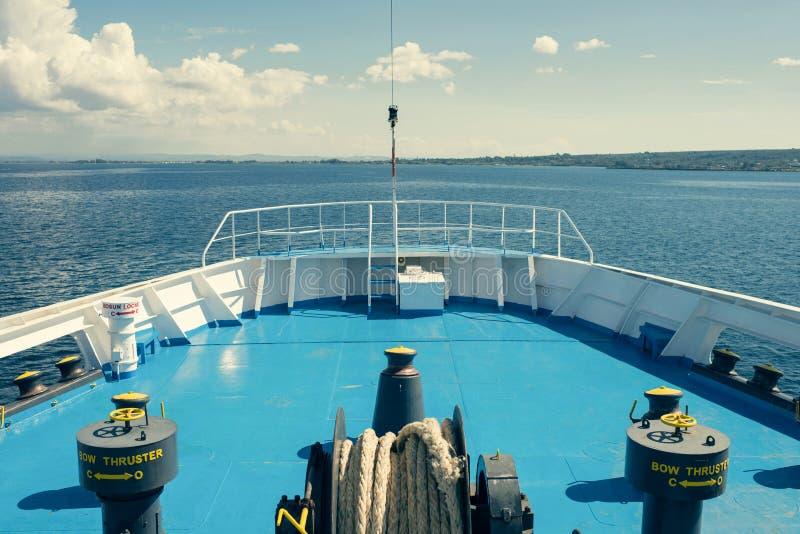 Eine große Antriebsscheibe mit aufgerollter Trosse auf der offenen Plattform der Fähre auf dem Meerblickhintergrund Sommerkreuzfa stockbild
