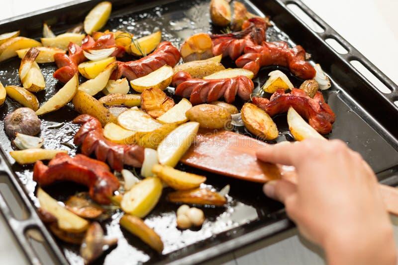 Eine große Bratpfanne mit fetthaltigen Nahrungsmitteln: Würste, Kartoffeln in einer rustikalen Art Hand und hölzerne Spachtel lizenzfreie stockfotos