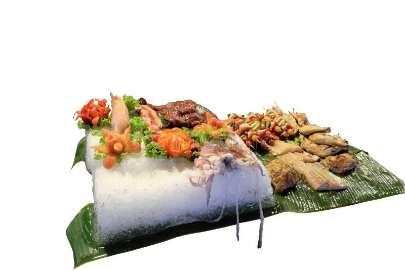 Eine große Eisscholle mit Frischfleisch, Fischen, Gemüse und Krake, gekochtes Essen, lokalisierter, weißer Hintergrund stockbild