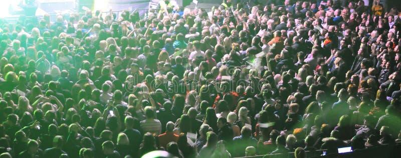 Eine große Menge von Leuten an einem Konzert in den Strahlen von Farbmusik lizenzfreie stockfotos