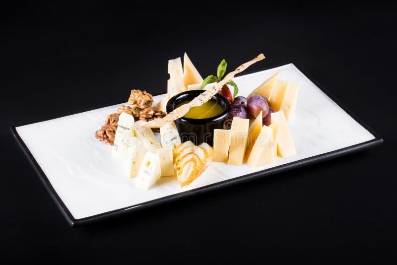 Eine große Platte mit einer breiten Auswahl von Snäcken mögen Trauben, Käse, Walnüsse, Cracker auf dunklem Hintergrund lizenzfreies stockbild