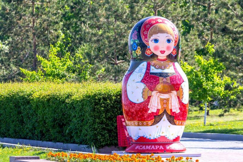 Eine große schöne Volkspuppe steht auf dem die Wolga-Damm lizenzfreie stockbilder