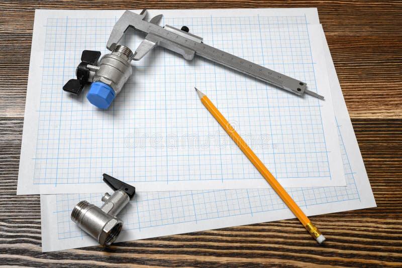 Eine große Spannschiene, die auf Millimeterpapier mit zwei Kugelventilen und einem Bleistift dazu liegt auf Holztisch liegt lizenzfreie stockfotografie