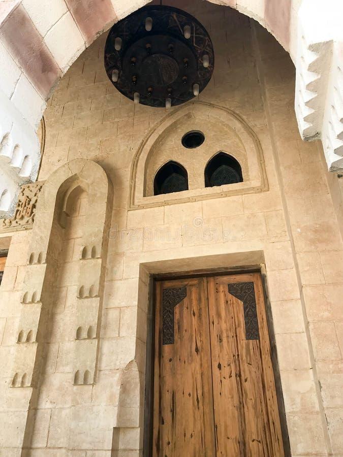 Eine große starke Holztür in einem Steinbogen mit einem Leuchter am Eingang zur arabischen islamischen Moschee, ein Tempel lizenzfreie stockbilder