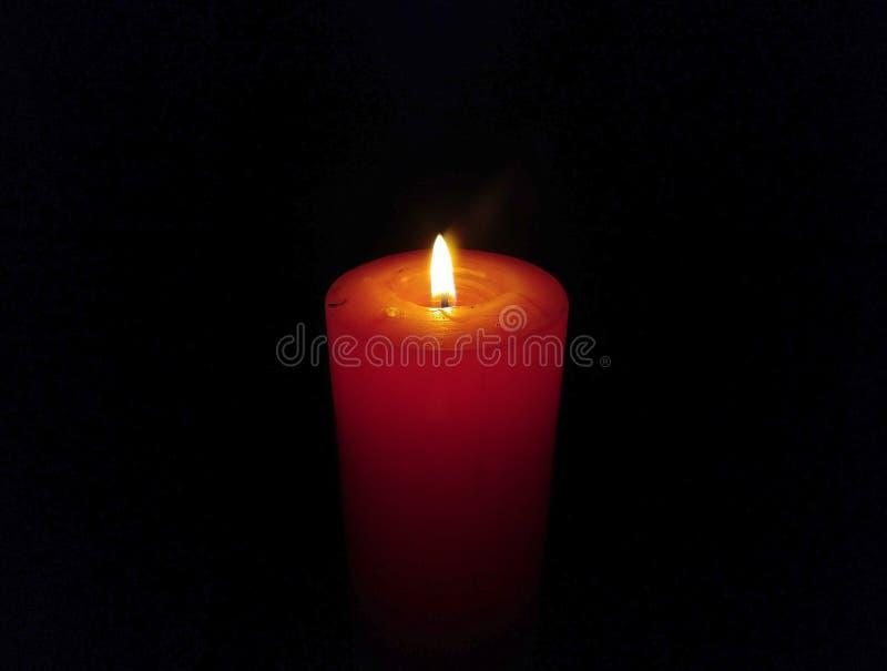 Eine gro?e Wachs-Kerze brennend lokalisiert auf schwarzem Hintergrund lizenzfreies stockfoto