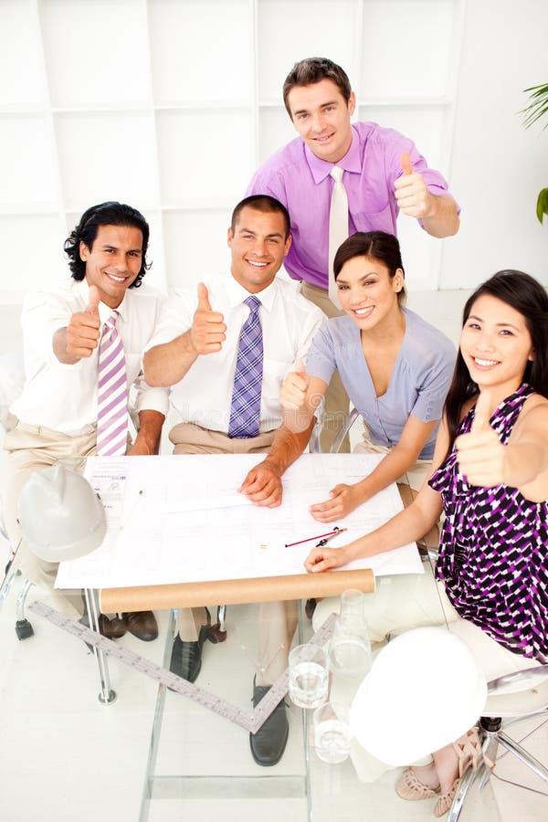 Eine Gruppe Architekten mit den Daumen oben in einer Sitzung stockfotografie