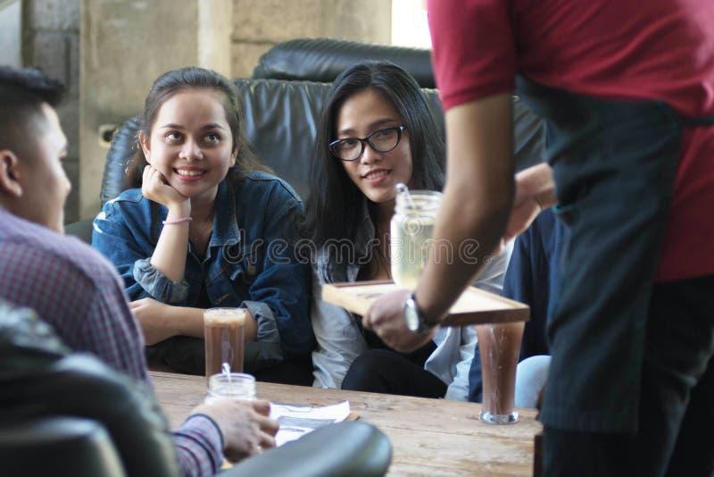 Eine Gruppe des jungen glücklichen Freunds empfängt Nahrung und Getränk von den Kellnern und vom Server am Café und am Restaurant stockfoto