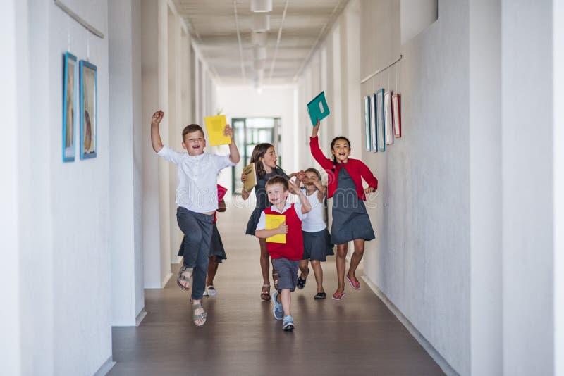 Eine Gruppe fröhlicher kleiner Schulkinder im Flur, die laufen und springen stockfotografie