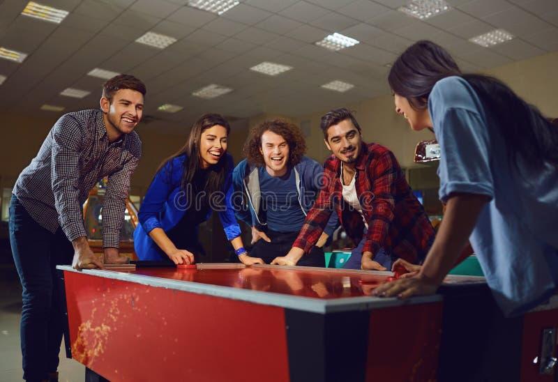 Eine Gruppe Freunde, die Lufthockey spielen lizenzfreies stockfoto